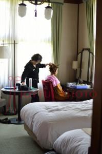 鏡の前で奈良ホテルのひとに成人式の支度をしてもらっている女性