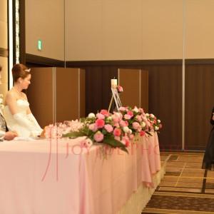 披露宴で来賓のスピーチを聞く新郎と新婦